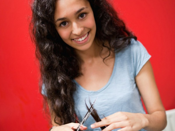 Selbsbewusste junge Friseurin schneidet Haare