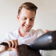 Glücklicher Friseur föhnt Haare