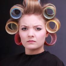 Unglückliche Frau mit Lockenwicklern im Haar