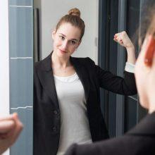 Selbstbewusste Dame vor dem Spiegel mit Siegerpose
